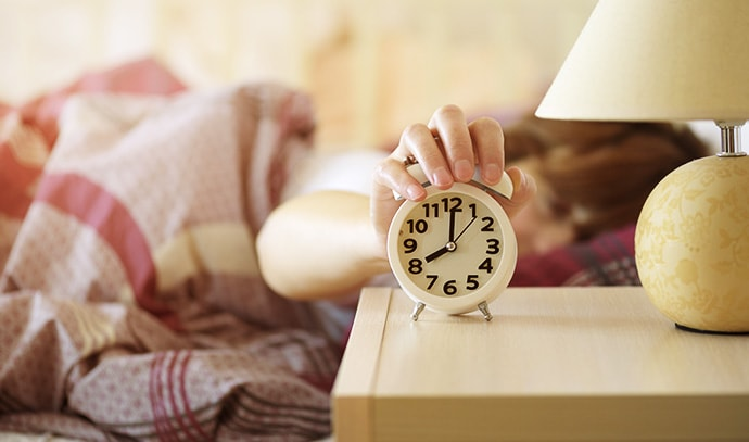 woman-waking-up-turning-off-the-alarm-clock