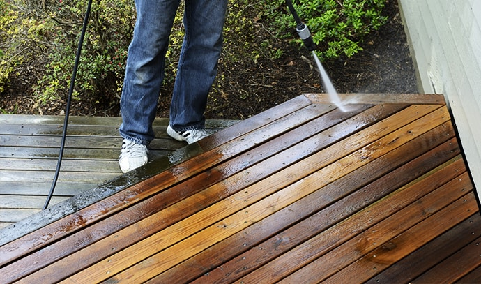 man-cleaning-deck-using-pressure-washer