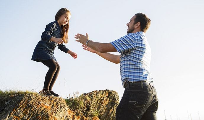 father-catches-leaping-daughter-cliff-sunset-setting