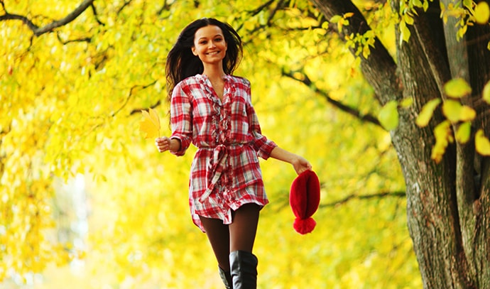 woman-checkered-dress-boots-walking-autumn-leaves-forest