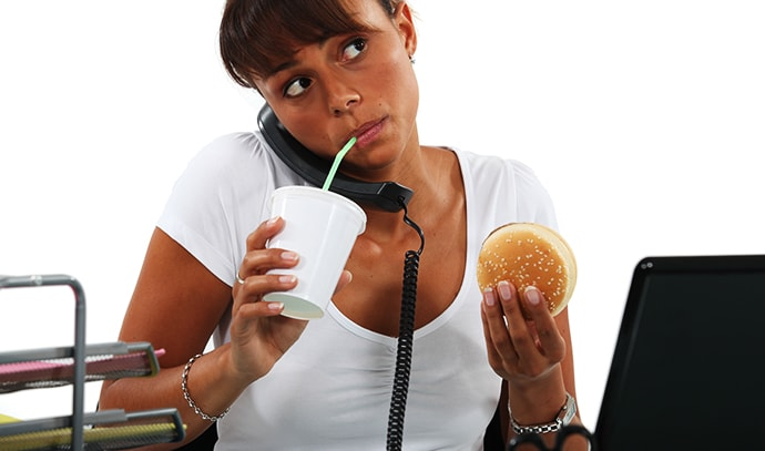 young-woman-eating-hamburger-drinking-straw-making-call