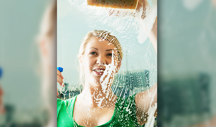 young-woman-cleaning-windows-spray-sponge