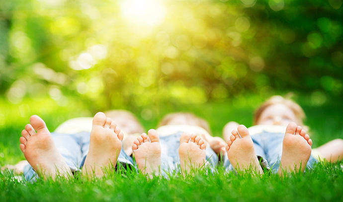 kids-triplets-laying-outside-green-lawn-small-feet
