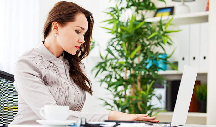 woman-sitting-office-using-laptop-business