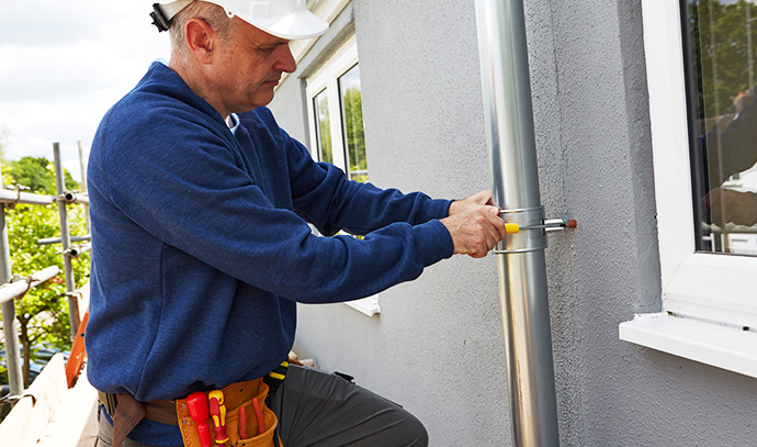 workman-replacing-guttering-exterior-house-sidewall-clamping