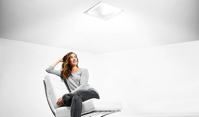 solatube-woman-sitting-comfortable-modern-white-chair-bright-skylights