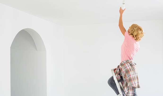 woman-ladder-fitting-light-bulb-new-house-ceiling